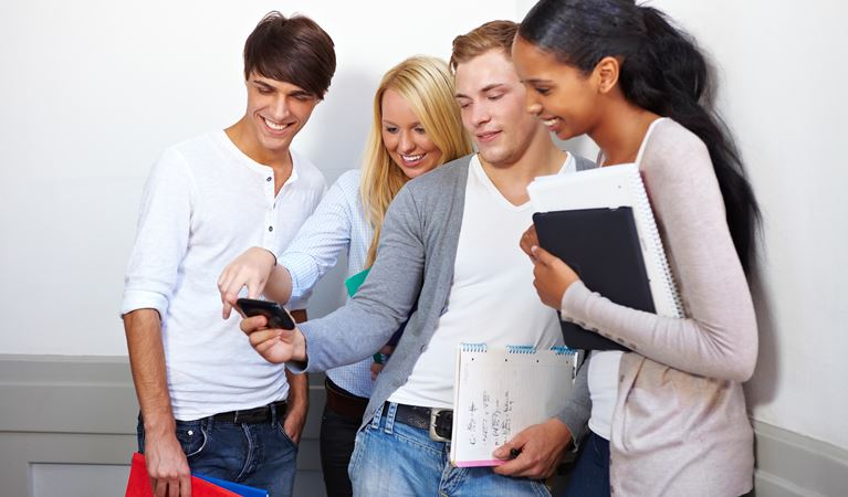 shutterstock 85369111%5b1%5d happy students looking at photos on smartphone